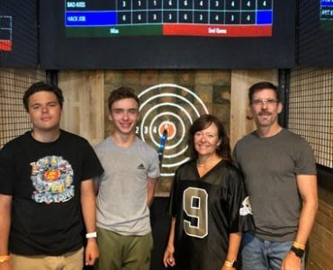 four people at axe throwing lanes